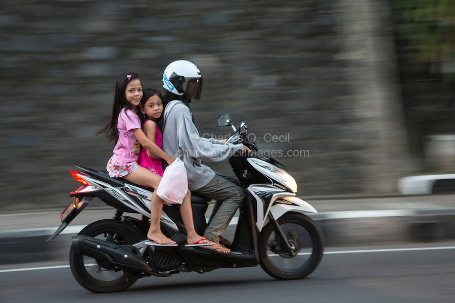 Bali, Indonesia.  Woman and Girls on Motor Bike, Klungkung, Semarapura.