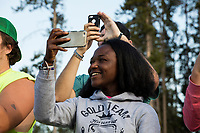 """Emmanuella Amanfo, of Italy, (center) smiles while watching Old Faithful erupt in Yellowstone National Park, Wyoming, USA. This was Amanfo's first visit to the US and Yellowstone. Asked about her impression of the park, she said, """"I've never seen anything like this."""" In the days surrounding when this image was taken, the geyser averaged an eruption about every 90 minutes, though occasionally there were hours between eruptions."""