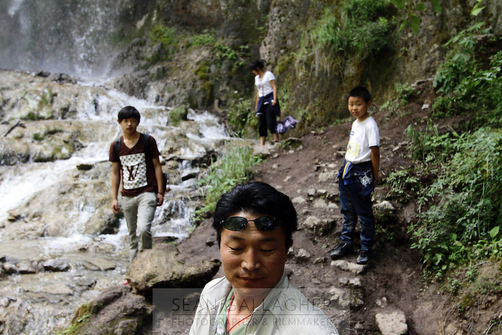 Tourists exploring a waterfall in the Jiuzhaigou National Park. Sichuan Province. China. 2011