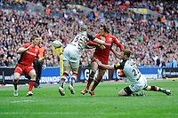 Alex Goode of Saracens offloads to David Strettle of Saracens as he is tackled by Rory Clegg (right) and Mike Brown of Harlequins during the Aviva Premiership match between Saracens and Harlequins at Wembley Stadium on Saturday 31st March 2012 (Photo by Rob Munro)