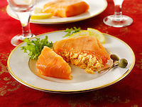 Smoked salmon parcel filled with cream cheese and cream cheese and crab, in a party buffet setting.