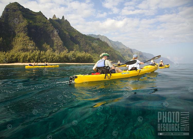 Sea kayakers paddling down Kauai's Na Pali coast in a group tour