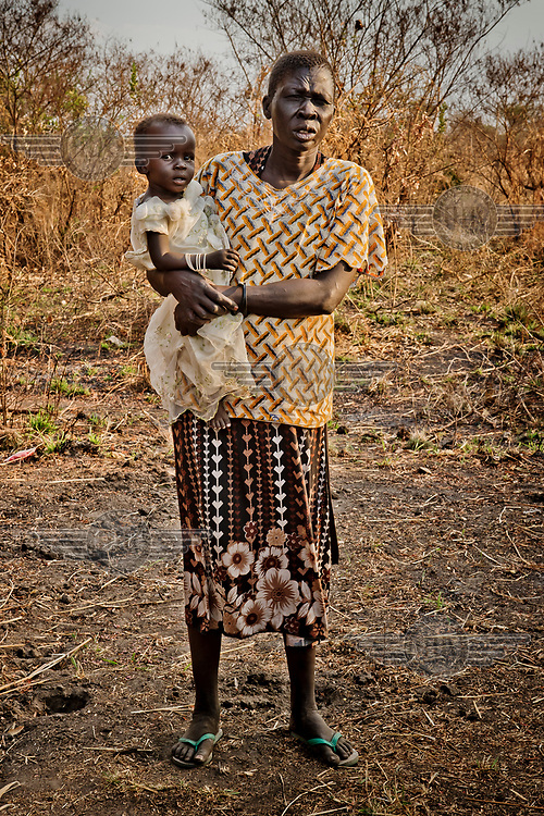 Adhieu Akol, who is partially sighted, holding her granddaughter Adut Ajak, whose mother is dead and her father's whereabouts are unknown, at the Nyumanzi settlement.