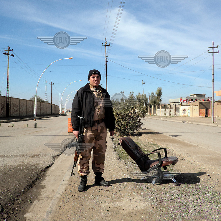 An Iraqi soldier from the Babylon Brigade guards the Mar Behnam Monastery in the village of Khidr Ilyas.