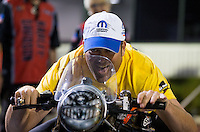 Nov 10, 2013; Pomona, CA, USA; NHRA pro stock driver Jeg Coughlin Jr sits on the pro stock motorcycle of Eddie Krawiec (not pictured) following the Auto Club Finals at Auto Club Raceway at Pomona. Mandatory Credit: Mark J. Rebilas-