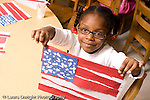 Preschool ages 3-5 proud girl holding up US flag she made from torn paper strips of paper glued to another sheets with painted starts horizontal