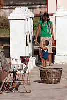 Myanmar, Burma. Shwezigon (Shwezegon)  Pagoda, Nyaung Oo, near Bagan.  Mother TEaching Little Boy to Strike Temple Bell with Wooden Mallet.
