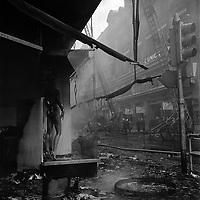 """Edifice commercial et de bureaux, magasin """"Au gaspillage"""" au début du XXe siècle, """"Au bon marché de Paris, """"le Printemps"""" et les assurances """"Le continent"""" dans les années 1960, """"Bouchara"""", """"Zara"""", 47 rue d'Alsace-Lorraine. 11 Mars 1964. Vue de l'incendie de l'immeuble du Printemps avec l'intervention des pompiers : le premier niveau ravagé par les flammes, un manequin brûlé debout dans la vitrine cassée ; la grande échelle au milieu de la rue, quelques pompiers autour, des badauds abrités devant la façade de l'immeuble en face."""