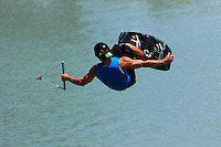 An extreme wakeboarder preforms a manouver in the air while grabbing his board.