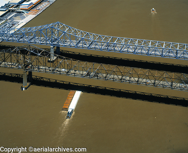 aerial photograph of a barge passing the under Crescent City Connection bridge, formerly known as the Greater New Orleans bridge, a suspension bridge spanning Mississippi River, New Orleans, Louisiana