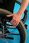 hand of young woman gripping on rim of her wheelchair