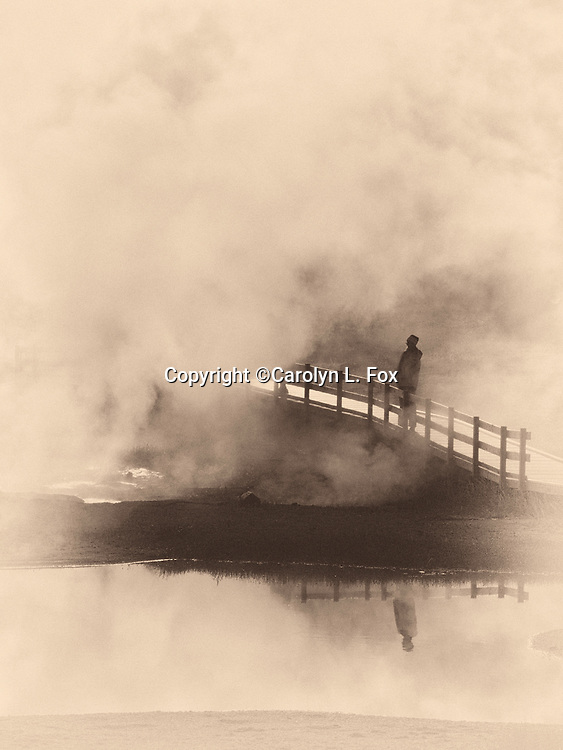 A person stands on a bridge as steam rises from a geyser in Yellowstone National Park.