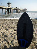 A skim board sits in the sand on the beach at Hunnington Pier in California.
