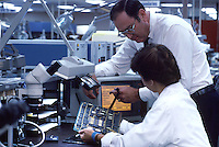 Technician and supervisor with monitor and computers which are used to evaluate circuit boards. Freeport Texas.