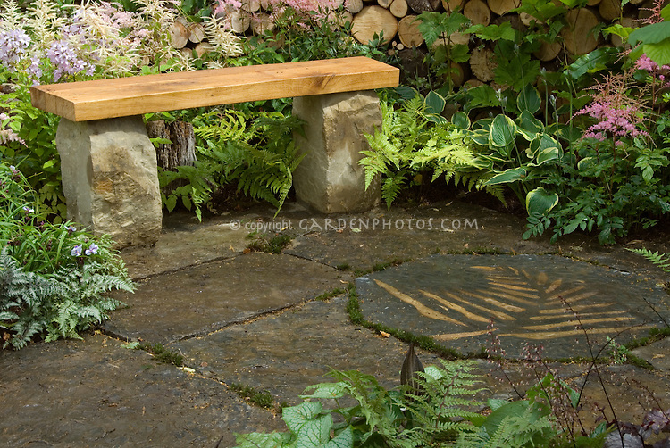 Wooden and stone garden bench on stone patio with leaf design in floor, with ferns, Brunnera, Astilbe in bloom, hostas, in a mostly shaded garden