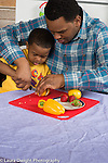 3 year old boy at home with father, in kitchen, learning how to cut vegetable