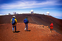 Hikers stand on the summit of Mauna Kea, Big Island of Hawaii with astronomical observatories in the background.