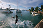 Children jumping from the jetty of the marina. La Digue island.