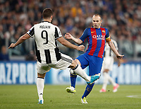 Football Soccer: UEFA Champions UEFA Champions League quarter final first leg Juventus-Barcellona, Juventus stadium, Turin, Italy, April 11, 2017. <br /> Juventus Gonzalo Higuain (l) in action with Andrés Iniesta (r) during the Uefa Champions League football match between Juventus and Barcelona at the Juventus stadium, on April 11 ,2017.<br /> UPDATE IMAGES PRESS/Isabella Bonotto