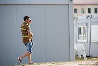 Zentrale Auslaenderbehoerde und BAMF-Aussenstelle in Eisenhuettenstadt.<br /> Bundesinnenminister Thomas de Maiziere und brandeburgs Ministerpraesident Dietmar Woidke besuchten am Donnerstag den 13. August 2015 die Zentrale Auslaenderbehoerde und BAMF-Aussenstelle in Eisenhuettenstadt. Sie liessen sich von Mitarbeitern die Situation in der Einrichtung zeigen und erklaeren, sprachen mit Fluechtlingen und besichtigten das auf dem Gelaende befindliche Abschiebegefaengnis.<br /> Der Besuch des Bundesinnenministers und des Ministerpraesidenten wurde von etwa 40 Journalisten begleitet.<br /> Im Bild: Ein Vater mit seinem vor einem der Wohncontainer.<br /> 13.8.2015, Eisenhuettenstadt/Brandenburg<br /> Copyright: Christian-Ditsch.de<br /> [Inhaltsveraendernde Manipulation des Fotos nur nach ausdruecklicher Genehmigung des Fotografen. Vereinbarungen ueber Abtretung von Persoenlichkeitsrechten/Model Release der abgebildeten Person/Personen liegen nicht vor. NO MODEL RELEASE! Nur fuer Redaktionelle Zwecke. Don't publish without copyright Christian-Ditsch.de, Veroeffentlichung nur mit Fotografennennung, sowie gegen Honorar, MwSt. und Beleg. Konto: I N G - D i B a, IBAN DE58500105175400192269, BIC INGDDEFFXXX, Kontakt: post@christian-ditsch.de<br /> Bei der Bearbeitung der Dateiinformationen darf die Urheberkennzeichnung in den EXIF- und  IPTC-Daten nicht entfernt werden, diese sind in digitalen Medien nach §95c UrhG rechtlich geschuetzt. Der Urhebervermerk wird gemaess §13 UrhG verlangt.]