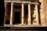 Bedouin sitting in front of Al Khazneh, an ancient rock-cut building in Petra, Jordan.