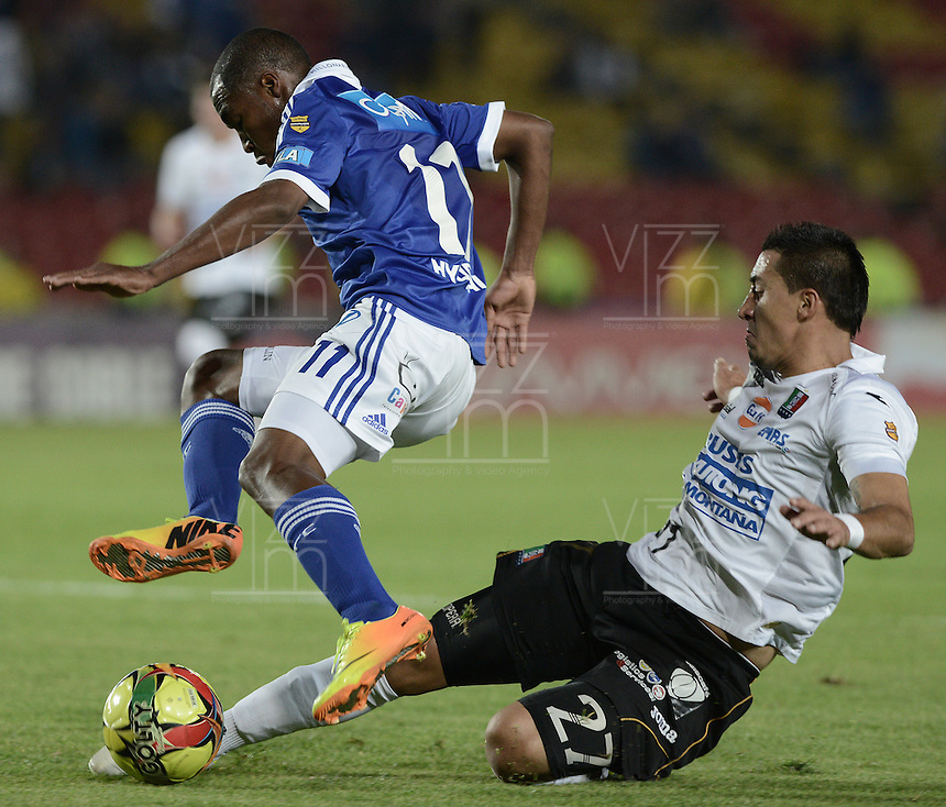 BOGOTÁ -COLOMBIA, 07-12-2013. Leudo Dhawling (Izq.) jugador de Millonarios disputa el balón con Jonathan Lopera Jimenez (Der.) jugador de Once Caldas durante partido por la fecha 6 de los cuadrangulares finales de la Liga Postobón  II 2013 jugado en el estadio Nemesio Camacho el Campín de la ciudad de Bogotá./ Leudo Dhawling (L) player of Millonarios fights for the ball with Jonathan Lopera Jimenez (R) player of Once Caldas during match for the 6th date of final quadrangulars of the Postobon  League II 2013 played at Nemesio Camacho El Campin stadium in Bogotá city. Photo: VizzorImage/Gabriel Aponte/STR