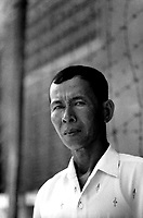 Prak Khan, a former interrogator at the S-21 Khmer Rouge detention centre at Tuol Sleng, where over 16,000 inmates were killed between 1975 and 1979. He is pictured in the grounds of Tuol Sleng,  his former workplace.