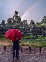 A rare Rainbow over the Bayon Temple in the Angkor Wat area; a World Heritage Site in Cambodia and the ever changing Weather during the Monsoon Season. A couple is watching the Rainbow over the Bayon Temple.