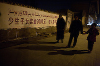 """People walk past a government billboard about money offered to Uighur families who have fewer children.  The text reads, approximately, """"Having fewer children rewards 3000yuan (about $450), that's 720yuan ($110) a person a year."""""""