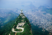 Corcovado, Rio de Janeiro, Brazil. Christ statue, aerial shot from behind with Sugar Loaf and Guanabara Bay.