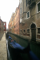 Moored and covered gondole in Venice canal<br />