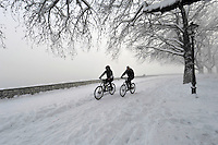 Pictured: Two cyclists ride next to the frozen over lake in Ioannina, northern Greece.<br /> Re: Heavy snow affects most parts of Greece