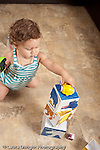 13 month old baby girl at home playing with toy vehicles and stacking boxes blocks putting vehicle on top of stack concept on top of vertical
