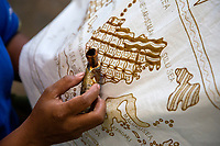 Yogyakarta, Java, Indonesia.  Batik Design Artist Applying Wax to Design Sketch on Cloth.  In this case the design is a map of ther Indonesian archipelago.