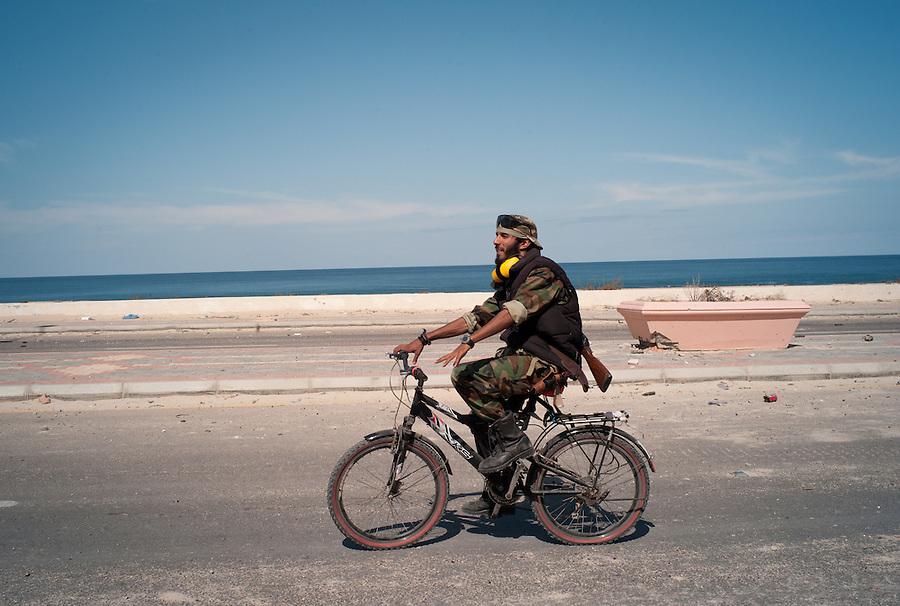 Anti-Gaddafi fighter rides a bicycle along the seaside in Sirte, Libya.