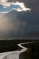 Vehicle travels the paved section of the Denali Park road during a summer rainstorm,  Denali National Park, Interior, Alaska.