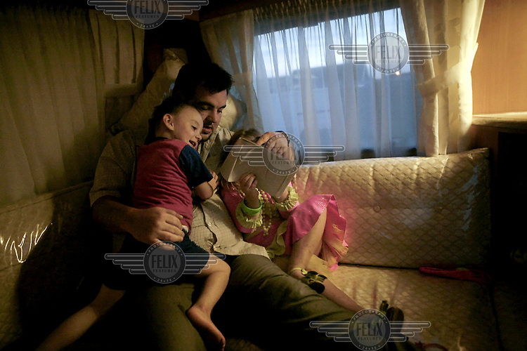 David Sheridan looks at drawings made by his daughter Viviana, with his son Richard on his knee in his trailer at Dale Farm, an Irish Travellers' site on a former scrapyard in Essex.