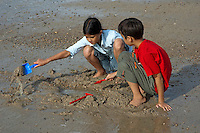 Brother and sister playing in the sand with spades, Anse du Guesclin, Brittany, France.