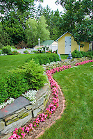 Home landscaping in backyard with shed house, stone wall with annual wax begonia flowers in pink, sweet alyssum, shrubs, picket fence, flowers, lawn grass, for graceful beautiful easy landscape