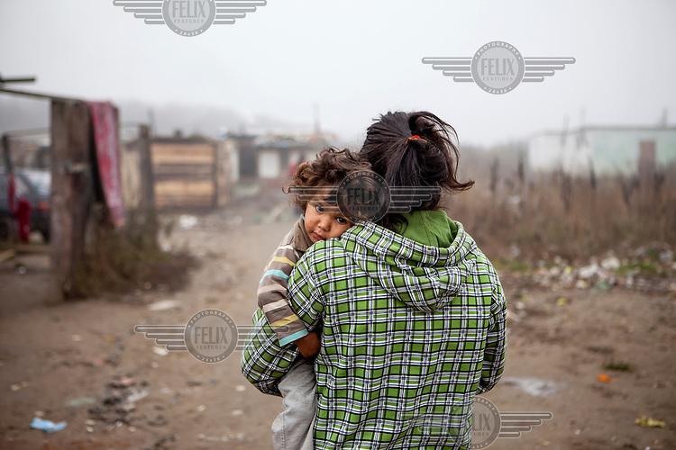 Elvira Ribarova carrying her child in the Roma settlement located in 'Budulovskej Street'.