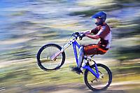 Rider pops a wheelie on mountain bike, Alberta, Canada