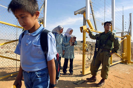 Israeli soldiers open a gate in the security fence to let school children cross the fence, returning from school to their village Jbara, October 28, 2003. The Palestinian village of Jbara was left on the Israeli side of the fence, 88 school children have to cross the new security fence on their way to school on the Palestinian side. Israeli Prime Minister Ariel Sharon defended his country's barrier from the Palestinians against European criticism yesterday, saying it was vital for Israel's security.