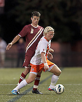 Syracuse University forward Emil Ekblom (14) dribbles as Boston College defender Chris Ager (2) defends.Boston College (maroon) defeated Syracuse University (white/orange), 3-2, at Newton Campus Field, on October 8, 2013.
