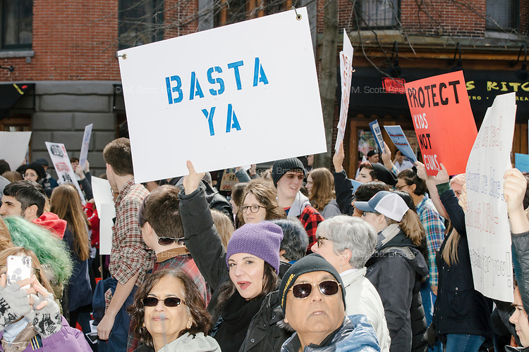"""People take part in the March For Our Lives protest, walking from Roxbury Crossing to Boston Common, in Boston, Massachusetts, USA, on Sat., March 24, 2018, in response to recent school gun violence. Here a woman holds a sign reading """"Basta Ya."""""""