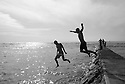 Jason Finlay and Joe Clark jumping off a jetty in Waikiki on Oahu in Hawaii