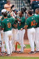 Zeke DeVoss #7 of the Miami Hurricanes is congratulated by his teammates after hitting a grand slam in the top of the 9th inning to give the Hurricanes a 10-5 lead over the Boston College Eagles during Game 4 of the 2010 ACC Baseball Tournament at NewBridge Bank Park May 27, 2010, in Greensboro, North Carolina.  The Eagles defeated the Hurricanes 12-10 in 12 innings.  Photo by Brian Westerholt / Four Seam Images