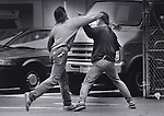 A couple of men fight each other on the streets of the tenderloin district of San Francisco, California.