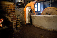 Olive oil extraction, Moulin a Huile, Entrevaux, Alpes de Haute Provence, France, Wednesday 24th February 2010. The mill room is heated by a fired oven, the temperature must be above 23 degrees for the oil to flow