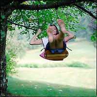 Young woman seated on tree swing<br />