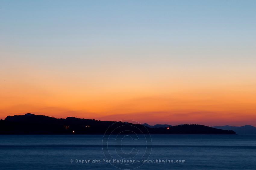 Sunset over the sea. View over the islands Daksa and others. House lights. Uvala Sumartin bay between Babin Kuk and Lapad peninsulas. Dubrovnik, new city. Dalmatian Coast, Croatia, Europe.